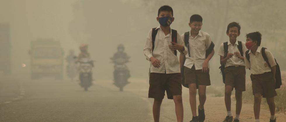 Kinder in Indonesien müssen auf ihrem Schulweg durch dichten Smog.