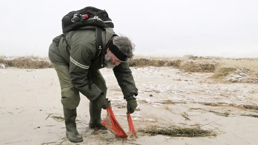 Plastikmüll im Meer: Naturschützer Thomas Clemens zieht Netzreste aus dem Sand von Mellum.