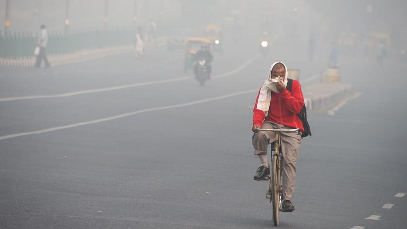 WHO: In Neu Delhi schützt sich ein Fahrradfahrer mit einem Tuch notdürftig gegen die Abgase.