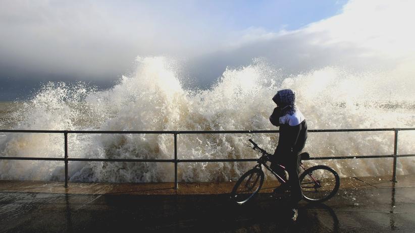 Klimawandel: Radfahrer an der britischen Küste: Dort könnte es künftig häufiger dazu kommen, dass Starkregen und Sturmflut gemeinsam auftreten.
