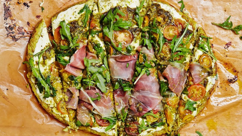 Glutenfreie Blumenkohl-Pizza mit Pesto, belegt mit Mozzarella, Prosciutto und frischem Rucola