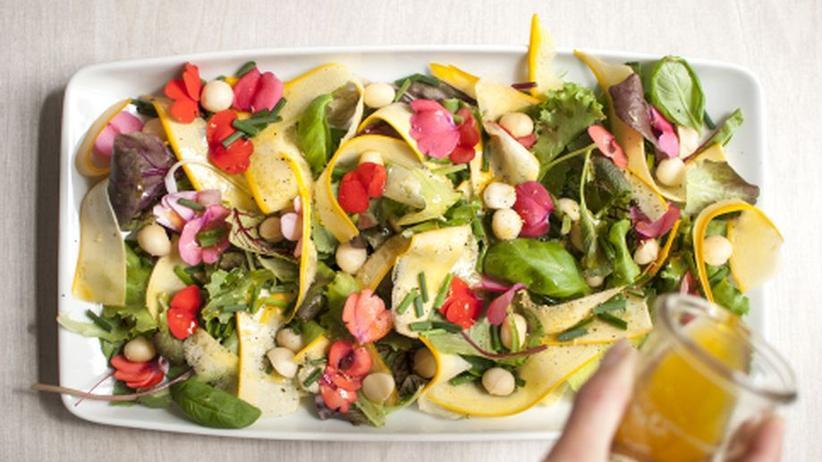 Bunter Gartensalat mit hauchdünnen Zucchinischeiben, essbare Blüten und zerlaufener Butter