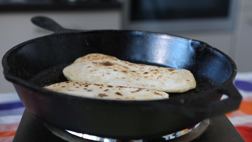 Dreierlei Hummus mit Naan: Die Teigfladen in der Pfanne backen, bis braune Punkte zu sehen sind.