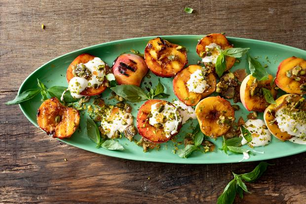 Berberitzen-Fleischbällchen: Zu den gegrillten Pfirsichen gibt es salziges Pistazienkrokant und eine Creme mit Vanille und Kardamom.