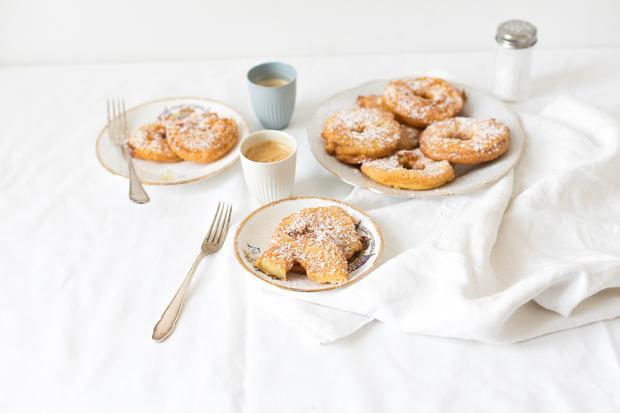 Gebackene Apfelradln mit Puderzucker: Im Teig für die gebackenen Apfelradln steckt nicht nur Mehl und Zucker, sondern auch Joghurt und Rum.