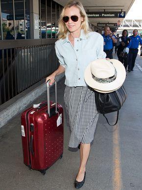 Gesellschaftskritik: Die Schauspielerin Diane Kruger mit Hut, Rock und Rollkoffer