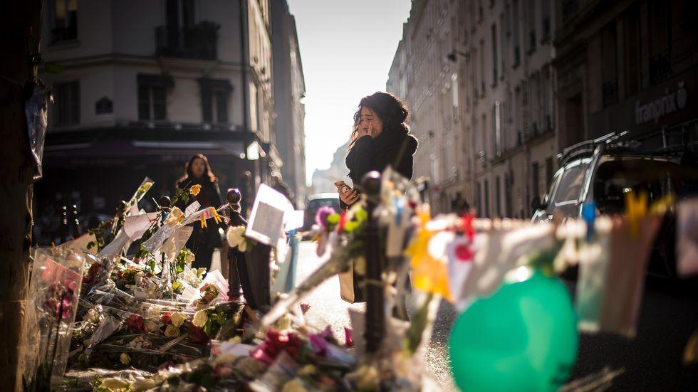 Paris: Nur wenige Tage nach den Anschlägen im November 2015 : Eine Frau weint angesichts der Blumen, Zeichnungen und Kerzen, die zum Gedenken an die Opfer der Attentate aufgestellt wurden.