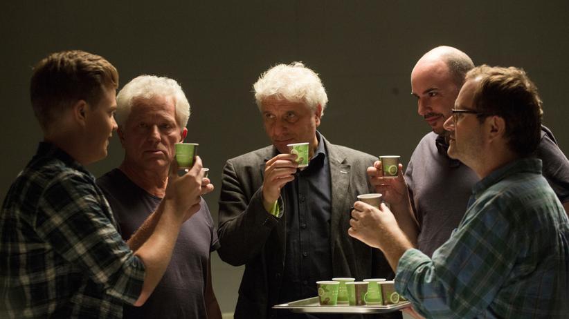 Das Team stößt mit Espresso in Pappbechern auf das 25-jährige Dienstjubiläum von Batic und Leitmayr an